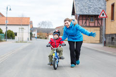 教她3岁的年轻母亲小儿子骑自行车 免版税库存图片