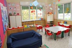 教室在有桌的一个幼儿园和椅子和蓝色沙发 免版税库存照片