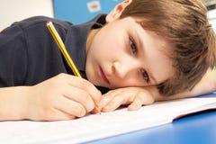 教室男小学生学习不快乐 免版税图库摄影