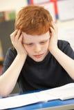 教室男小学生强调的学习 免版税库存图片