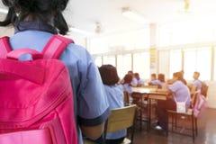 教室迷离,有来到classroo的红色背包的女孩 免版税图库摄影