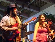 教导带的榜样歌手弹吉他并且唱歌 免版税图库摄影