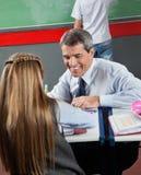 教小女孩的愉快的老师在书桌 库存图片