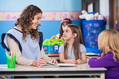 教小女孩的老师在教室 免版税库存照片