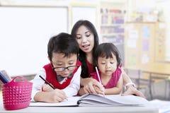 教师和儿童研究在教室 免版税图库摄影