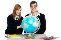 教师和学员查看地球 免版税库存图片