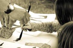 教师帮助的学员图画象形文字 库存照片