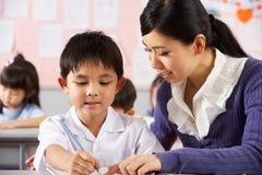 教师帮助的学员在中国学校 免版税库存照片
