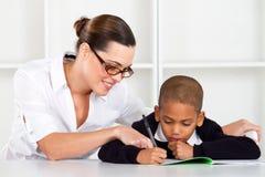 教师帮助的男小学生 免版税库存图片