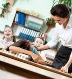 教师醒来休眠在服务台学生  免版税库存照片