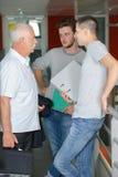 教授谈话与走廊的两名学生 免版税库存图片