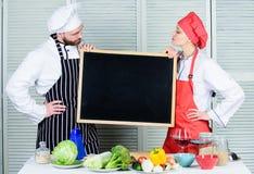 教的不同的烹调技术 男人和妇女藏品板夫妇在烹饪学院 主要厨师和预习功课 库存图片