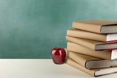 教科书、苹果和黑板 免版税库存照片