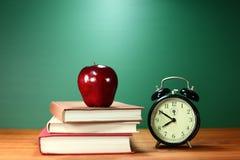 教科书、苹果计算机和时钟在书桌上在学校 免版税库存照片