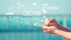教练与智能手机 库存图片