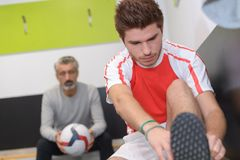 教练体育队谈话与足球运动员 免版税图库摄影