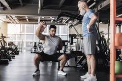 教练员与在现代健身房的老男性一起使用 免版税库存图片