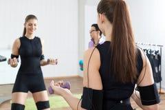 教练员协助女运动员做体操止血带锻炼 免版税图库摄影