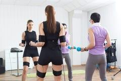 教练员协助女运动员做体操止血带锻炼 免版税库存图片