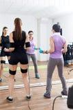 教练员协助女运动员做体操止血带锻炼 免版税库存照片