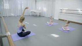 教练员和两个女孩裁缝时尚坐在芭蕾类的席子 股票视频