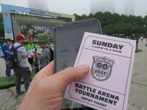 教练员Pokemon的争斗竞技场去费斯特用有电话和比赛词条票的手 免版税库存照片