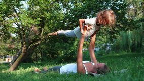 教练她的小逗人喜爱的女儿的年轻运动的母亲做瑜伽锻炼 影视素材