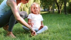 教练她的小逗人喜爱的女儿的年轻运动的母亲做瑜伽锻炼 股票视频