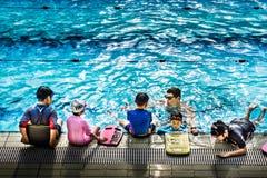 教练孩子的游泳辅导员由水池边 免版税图库摄影