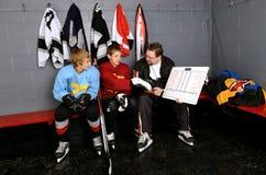 教练少年的曲棍球运动员 免版税库存图片