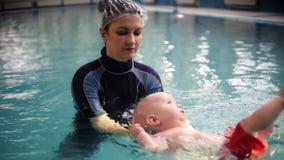 教练或母亲在水池教婴孩游泳 婴孩在它的后面说谎并且学会保持平衡和保持  影视素材