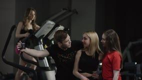 教练来到招呼到新的健身房的可爱的女孩并且要求做与他们的selfie与参与模拟器女孩  影视素材