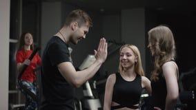 教练走向冷却新的健身房和上流的五女孩和询问的招呼他们与参与在的模拟器女孩 股票视频