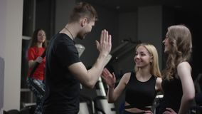 教练走向招呼到新的健身房和上流的五好女孩并且询问他们与参与在的模拟器女孩 股票视频