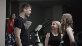 教练走向招呼到新的健身房和上流的五美丽的女孩并且询问他们与参与模拟器女孩 股票视频