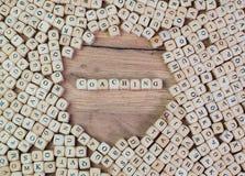 教练,教练的,在信件的词德国文本在立方体在桌上切成小方块 库存照片