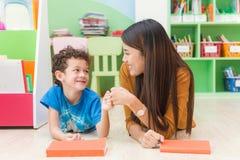 教美国孩子的年轻亚裔妇女老师在有幸福和放松的幼儿园教室 免版税库存照片