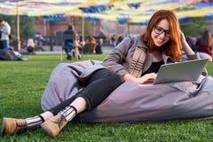 教育、技术和互联网概念-镜片的微笑的红头发人少年有便携式计算机的 库存图片