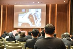 教育人和商人的被弄脏的图象坐在行业研讨会和演讲人的会议室的存在 免版税图库摄影