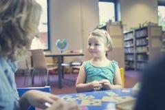 教育和乐趣 与打比赛的老师的孩子在教室 图库摄影
