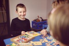 教育和乐趣 与打比赛的老师的孩子在教室 免版税图库摄影