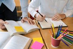 教育和学校概念,学生校园帮助机关朋友追赶的读书和检查和学会辅导 免版税库存图片