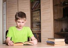 教育和学校概念 读bo的惊奇的男孩学生 免版税图库摄影