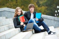 教育和学生 有笔记本的愉快的年轻大学生 图库摄影