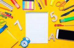 教育在一张书桌上的辅助部件在黄色背景 苹果登记概念教育红色 文教用品 手表,色的笔,电话,标志 笔记 免版税库存图片