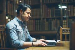 教育在欧洲 阿拉伯年轻英俊工作在老图书馆里 水平的构成 从旁边外形的看法 免版税库存照片