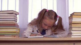 教育女孩猜测并且解决任务 考虑家庭作业的年轻白种人女孩 股票视频