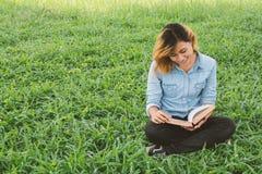 教育妇女 读一本书的年轻美丽的妇女在公园 库存照片