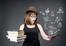 教育学校技术概念 有旧书的惊奇的书呆子学生在一个手和e读者上在别的在灰色backgro 免版税库存图片