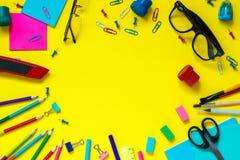 教育学生文具在黄色背景的玻璃静物画 免版税库存图片